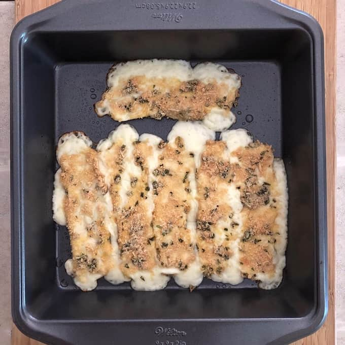 Melted baked mozzarella cheese sticks in baking pan.
