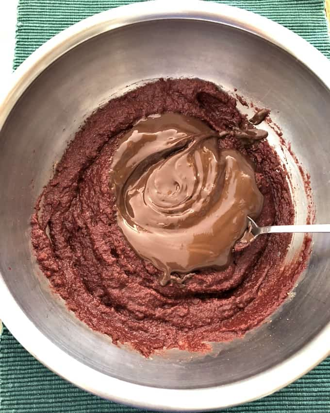 Mixing melted chocolate with beet brownie batter in stainless steel bowl.