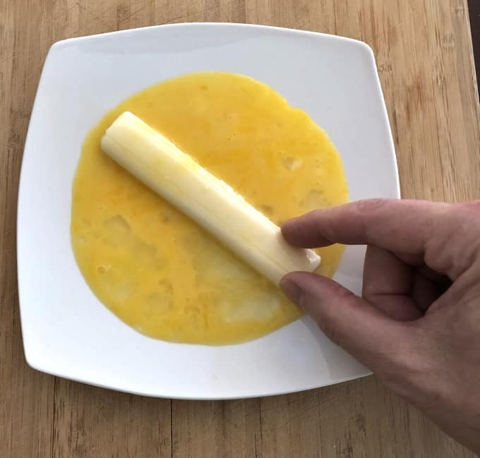 Rolling mozzarella cheese stick in egg in shallow white dish.