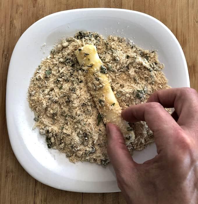 Rolling mozzarella cheese stick in flour-basil mixture in shallow white dish.