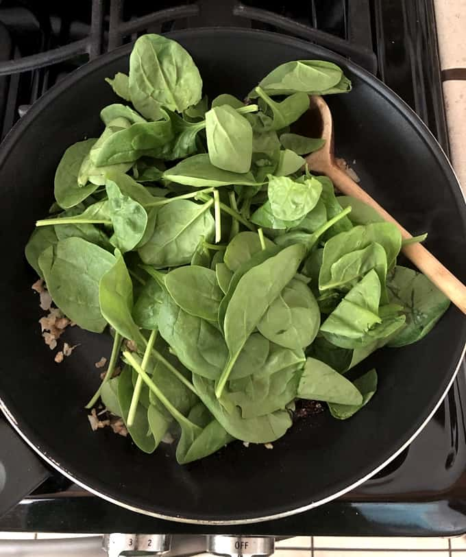 Cooking fresh spinach with chopped mushroom stems, shallots, garlic and sundried tomatoes in skillet with wooden spoon.