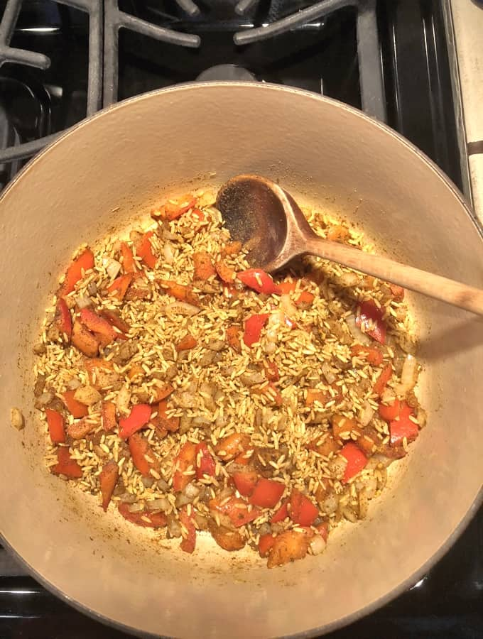 Heating rice, onion, red bell pepper and curry powder in skillet with wooden spoon.