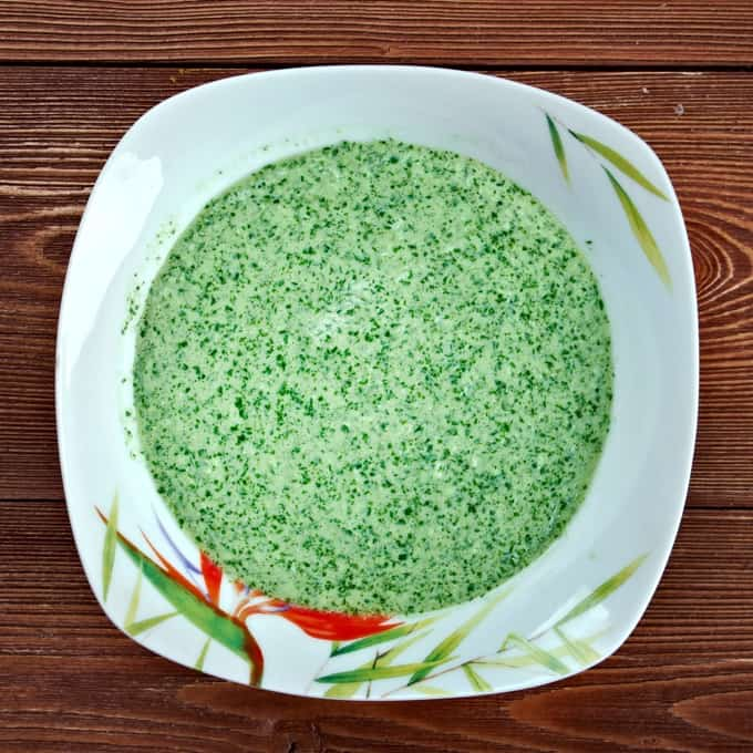 Spicy Peruvian aji verde in square white bowl on wooden table.