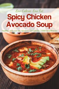 Spicy chicken soup garnished with avocado slices and fresh cilantro in brown ceramic bowl.