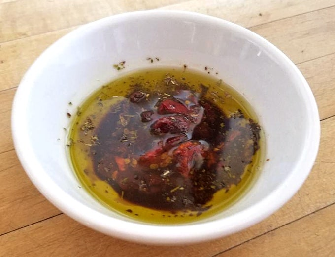 Sun-dried tomatoes with Herbs de Provence, olive oil and balsamic vinegar in small white bowl.