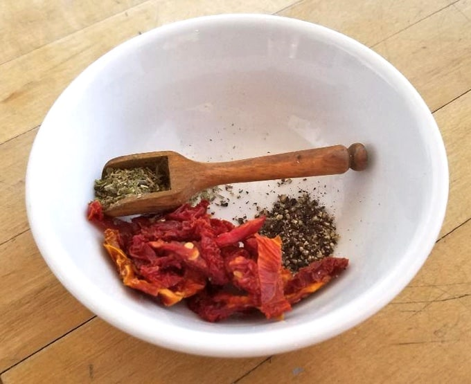 Chopped sun-dried tomatoes with Herbs de Provence in small white bowl with wooden spoon.