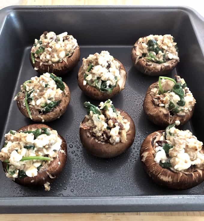 Unbaked vegetarian stuffed mushrooms in rimmed baking sheet.