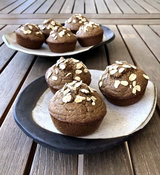 Vegan banana oat muffins on ceramic plates on wood table.