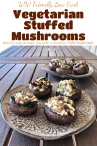 Two small plates with vegetarian stuffed mushrooms on wooden table.