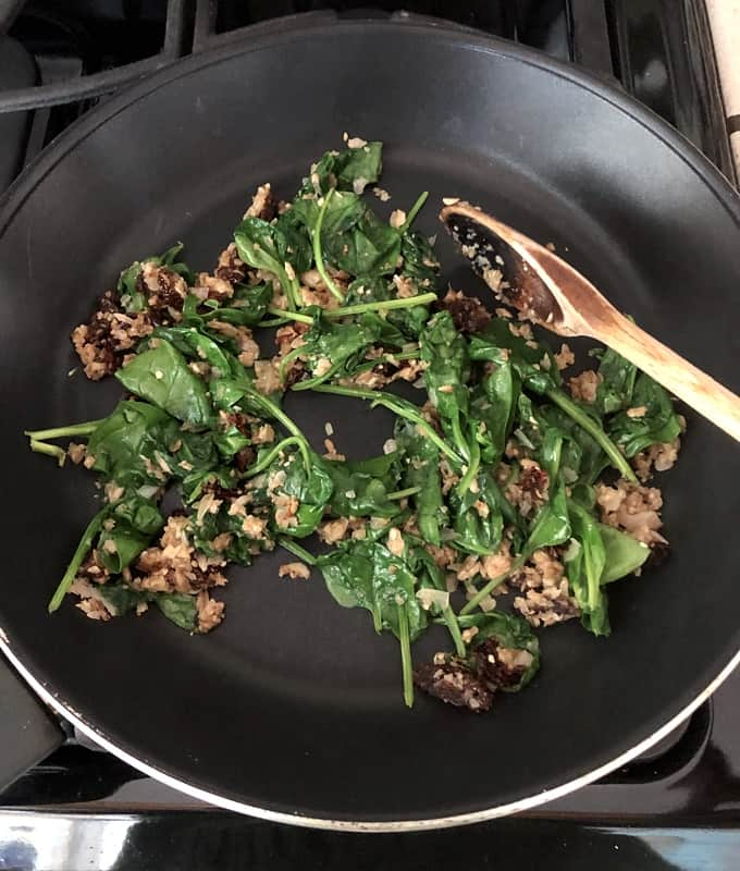 Wilted spinach with cooked mushroom, shallot, garlic and sundried tomato mixture in skillet with wooden spoon.