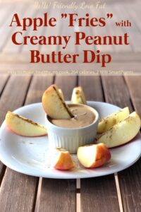 Cinnamon apple slices with creamy peanut butter dip in white plate.