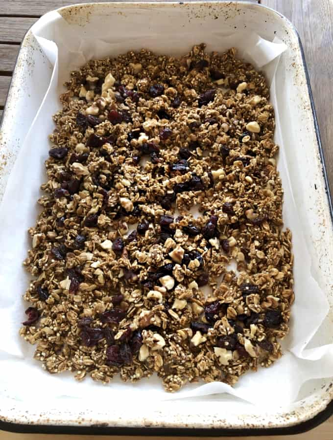 Fresh baked quinoa oat granola with raisins and dried cranberries in baking pan.