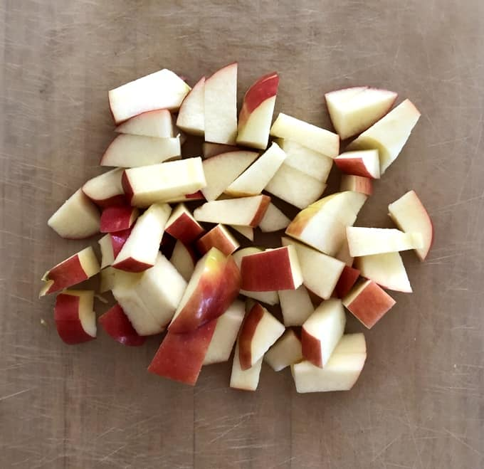 Fresh chopped apple chunks on wood cutting board.