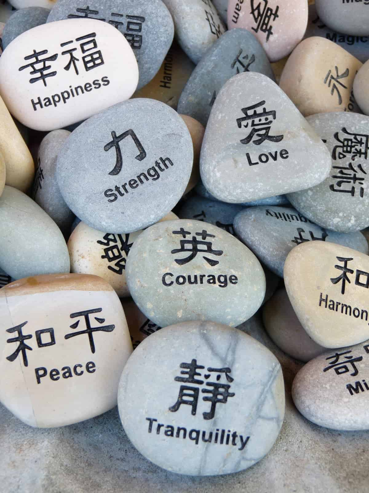 Inspirational words and Asian characters written on pile of colorful rocks.