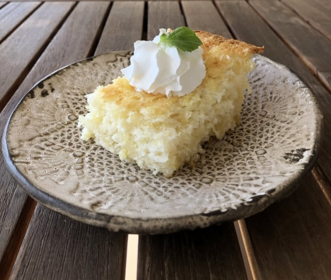 Piece of pineapple angel food cake with whipped topping and mint on ceramic plate.
