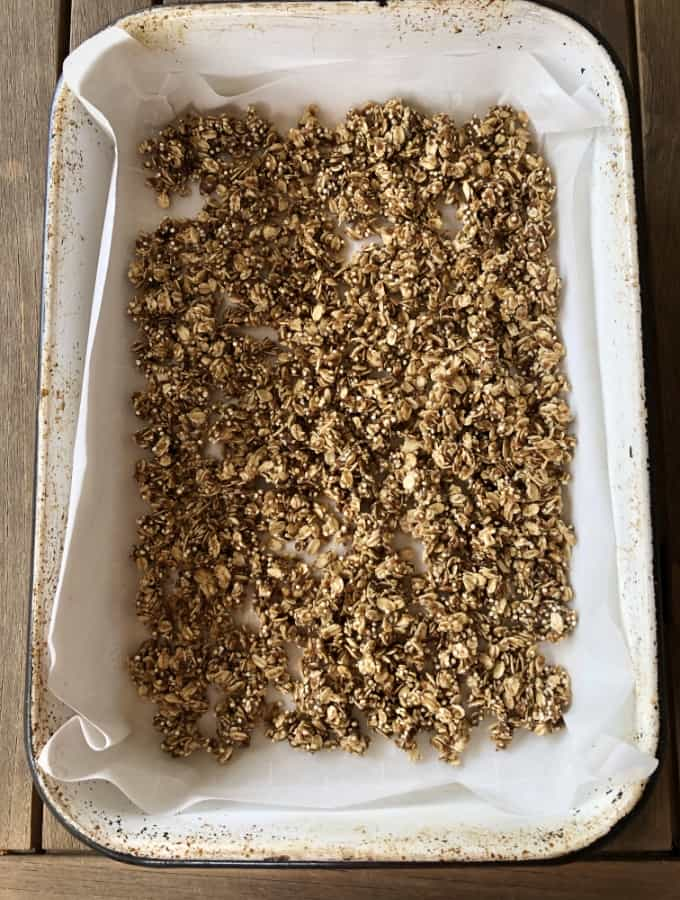 Quinoa oat granola in parchment lined baking pan.