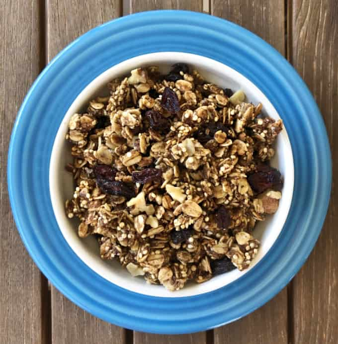 Quinoa oat granola with dried cranberries and raisins in white bowl on blue plate from above.