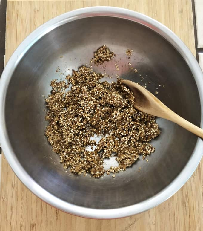 Mixing honey, brown sugar, ground flaxseeds, quinoa and sesame seeds in mixing bowl with wooden spoon.