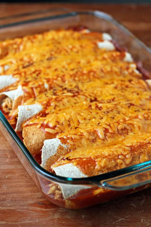 Chicken and bean enchiladas topped with cheese in glass baking dish.