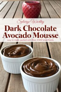 Creamy dark chocolate avocado mousse in white ramekins on wooden table with red candle.