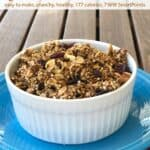 Quinoa oat granola in white ramekin on blue plate on wooden table.