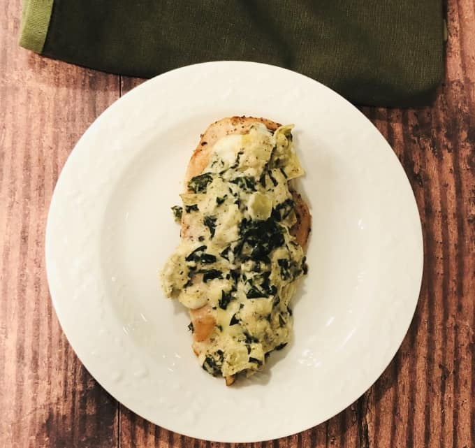 Chicken breast topped with spinach artichoke dip in white plate from above.