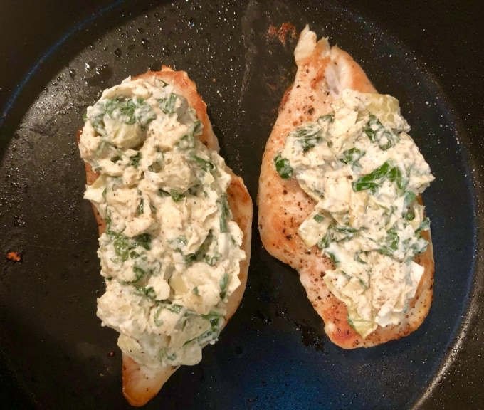 Two chicken breasts topped with spinach artichoke dip in skillet.