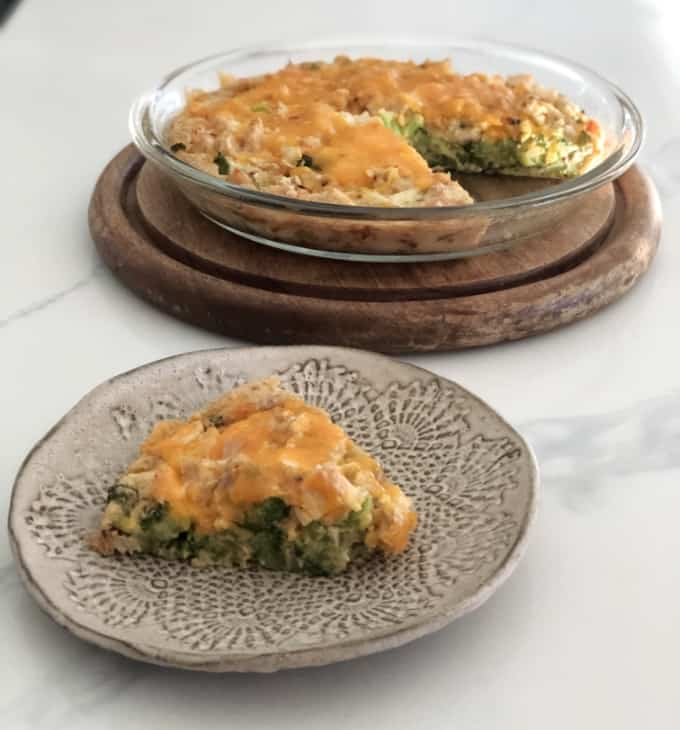 Slice of chicken broccoli pie on ceramic plate in front of remaining pie in glass pie dish.