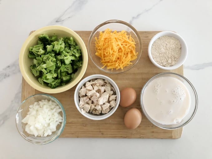 Chopped broccoli, onions, chicken, shredded cheese, two eggs, baking mix and milk in small bowls on wooden cutting board.