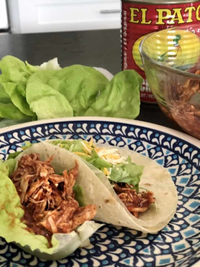 Chicken enchilada tacos in tortilla and lettuce wrap on blue plate.