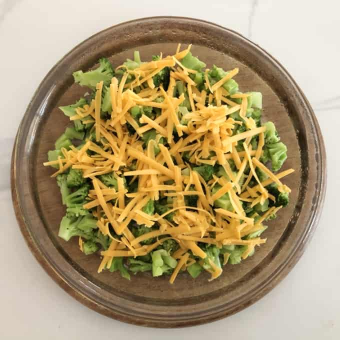 Chopped broccoli and shredded cheese layered in glass pie dish on round wooden cutting board.