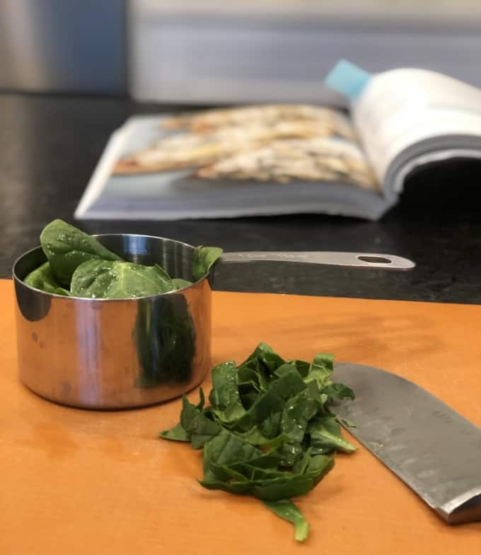 Chopping fresh spinach on orange cutting mat with open cookbook in background.