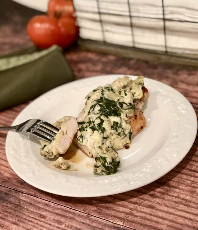 Spinach artichoke dip chicken breast on white plate with fork