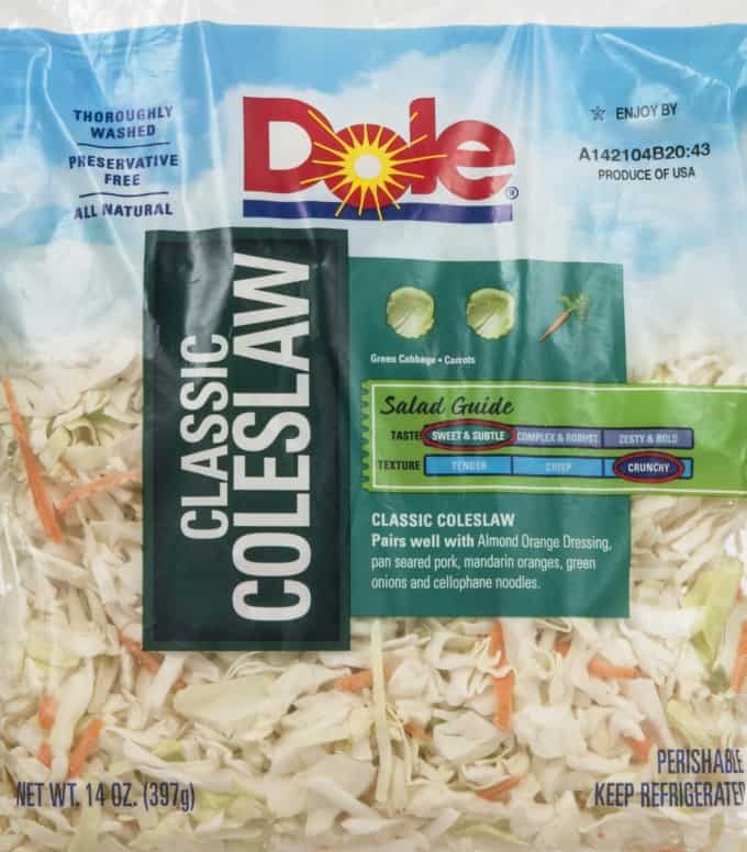 Bag of Dole classic coleslaw packaged mix with shredded green cabbage and carrots.
