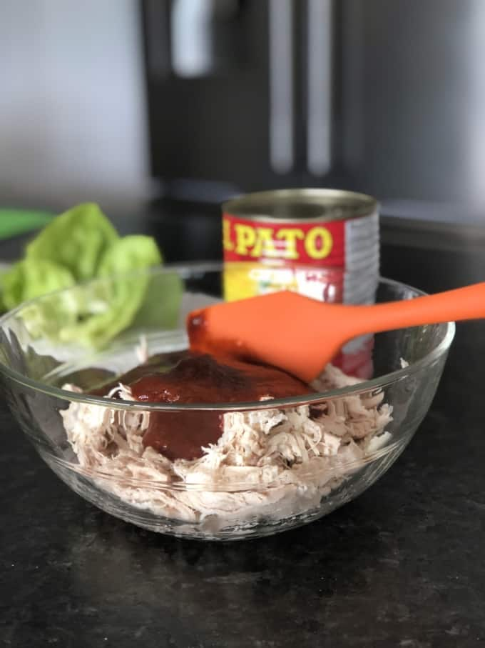 Mixing shredded chicken with red enchilada sauce in glass bowl.