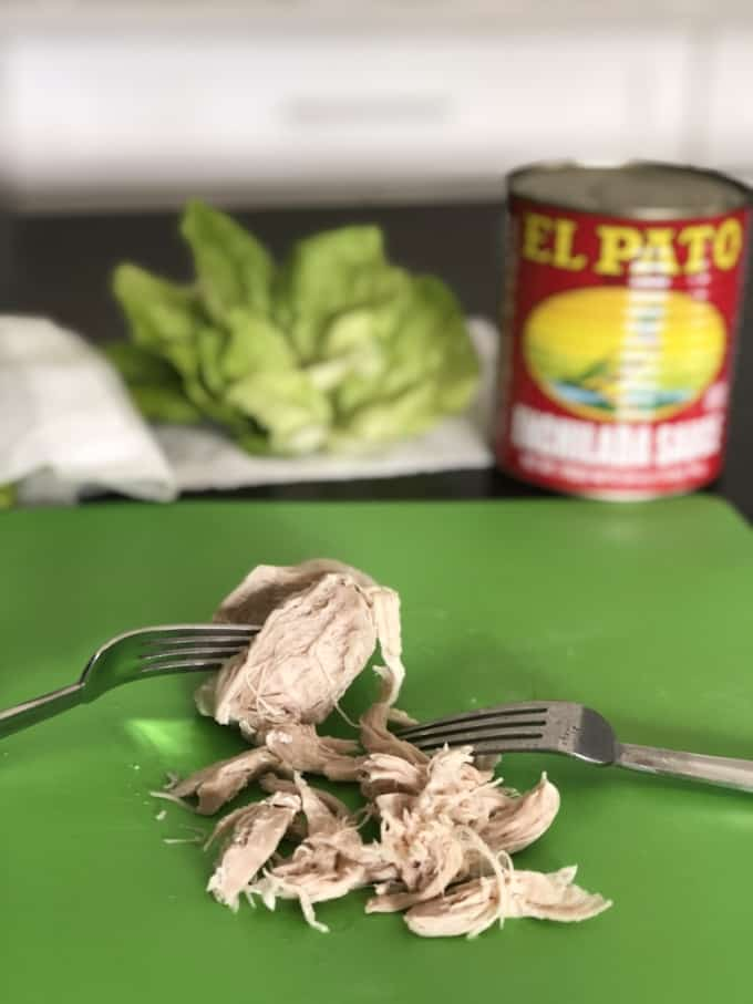Shredding chicken breast with two forks on green mat with lettuce leaves and can of enchilada sauce in background