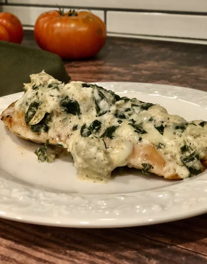 Spinach artichoke dip topped chicken breast on white plate with fresh tomatoes in background.