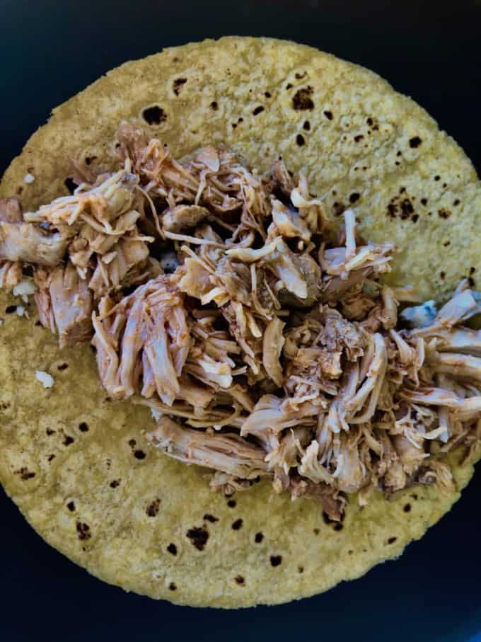 Heating tortilla with blue cheese and shredded chicken in skillet.