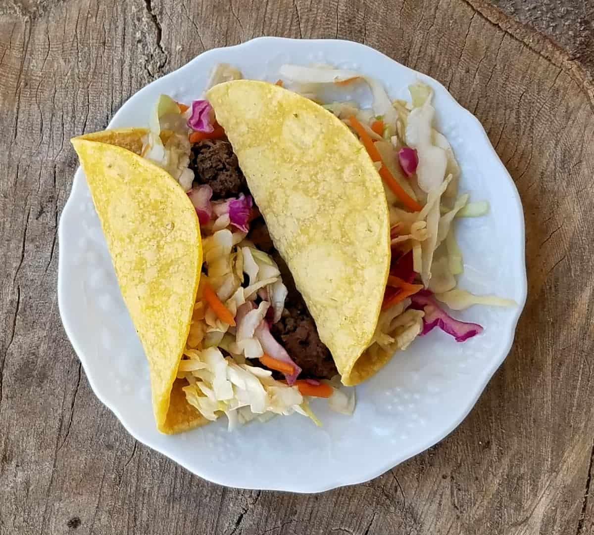 Two Asian spiced tacos on white plate on wood