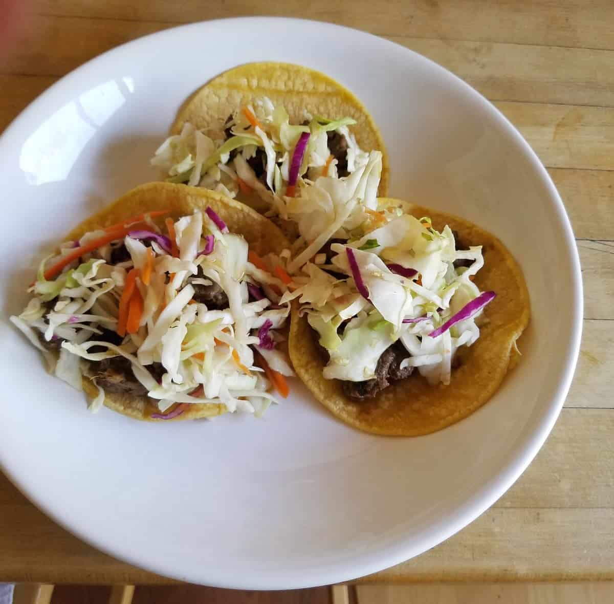 Three Asian pork tacos in white plate.