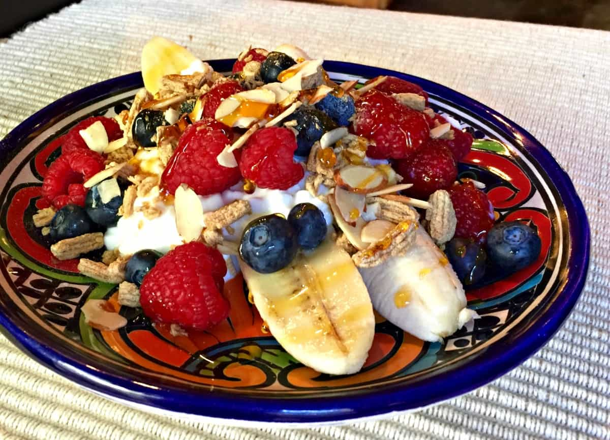 Sliced bananas with cottage cheese, blueberries, raspberries and sliced almonds drizzled with honey.
