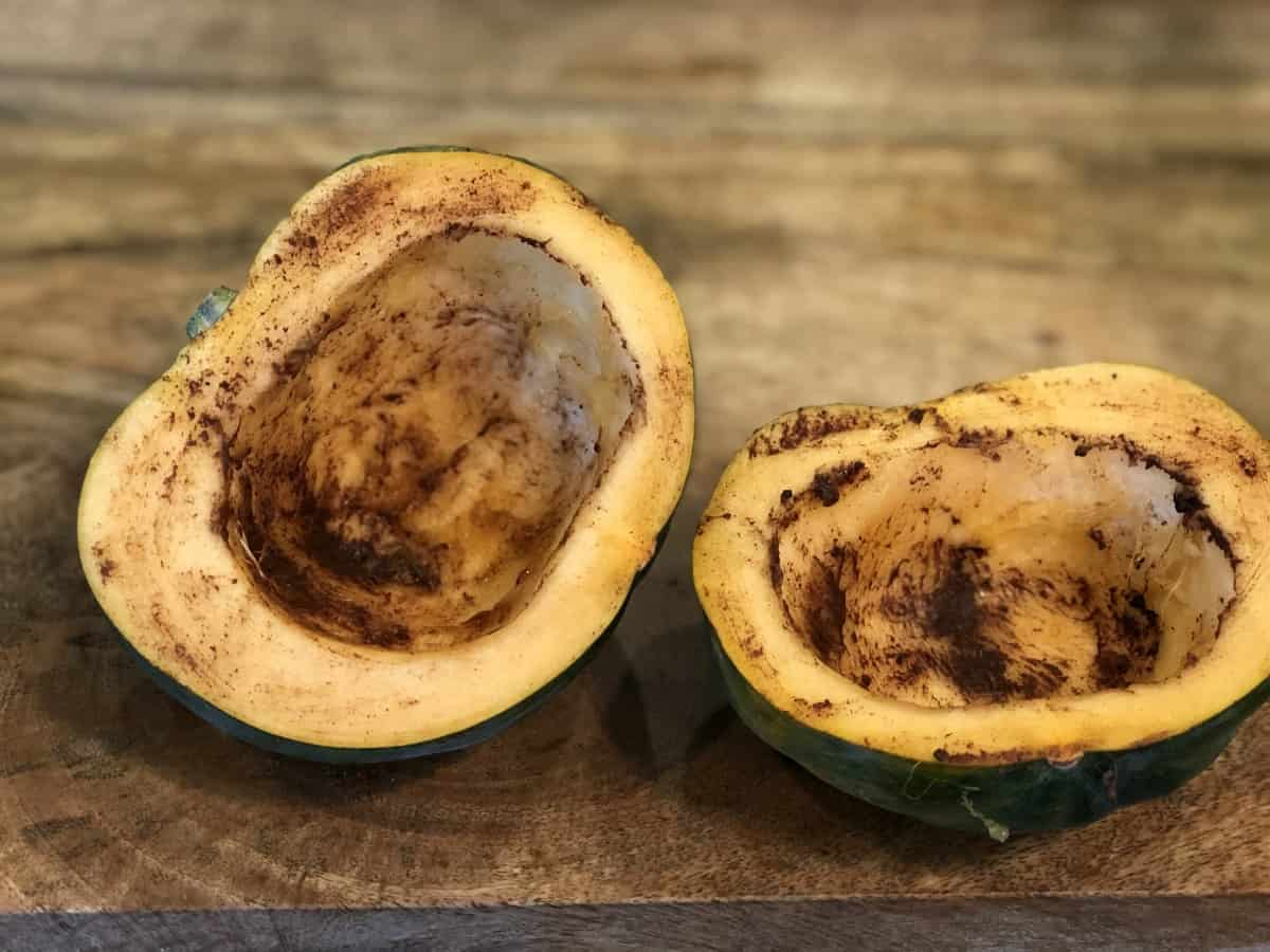 Acorn squash cut in half and rubbed with olive oil and pumpkin pie spice on wood cutting board.