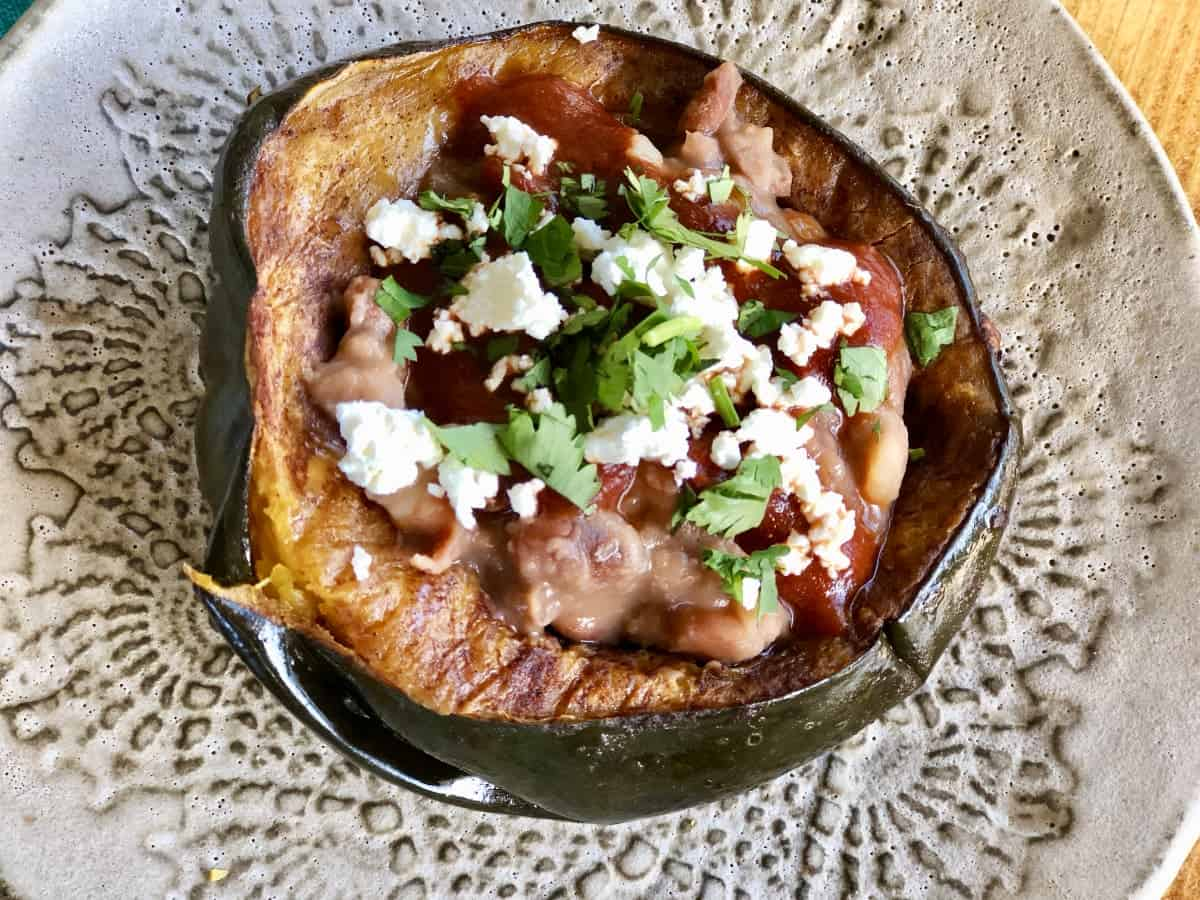 Roasted acorn squash topped with pinto beans, red chili sauce, crumbled cheese and chopped cilantro