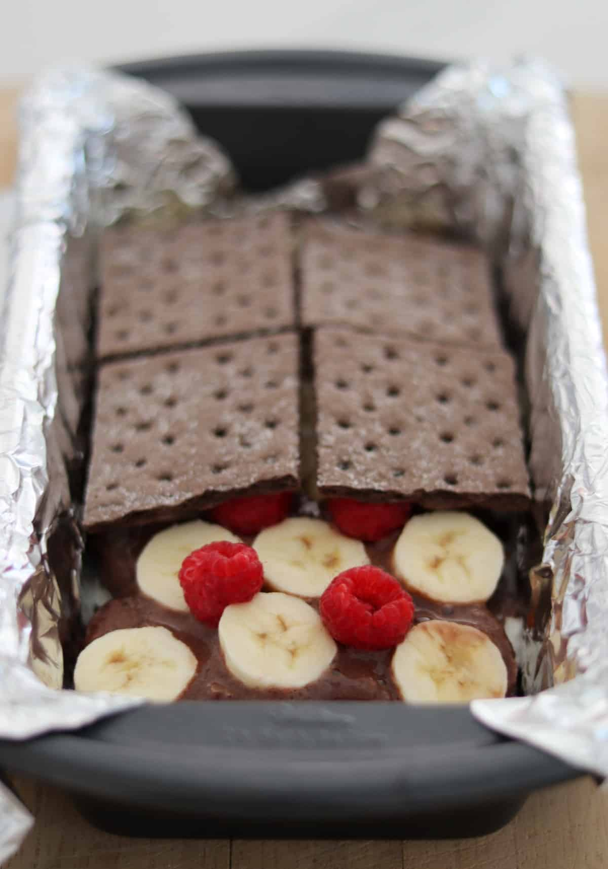 Loaf pan with layers of chocolate graham crackers, fudge ice cream bars, banana slices and raspberries.