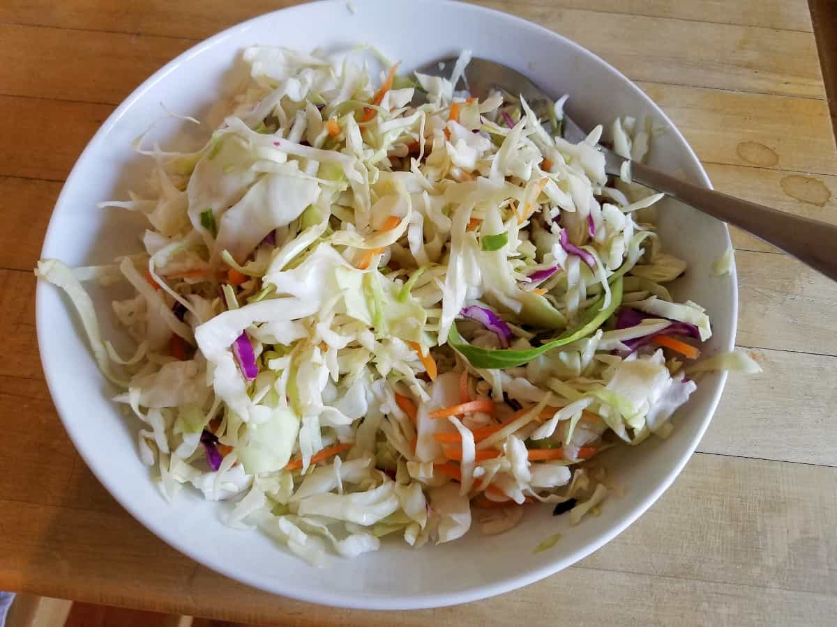 Cole slaw and rice vinegar mixed in white bowl with spoon.