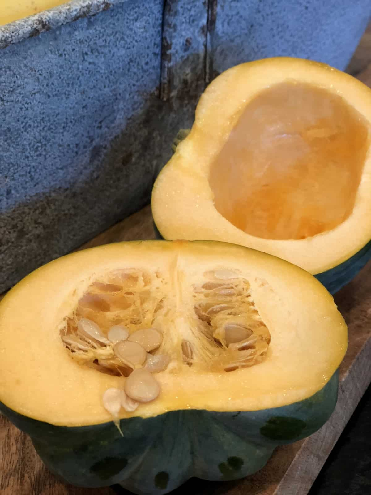 Acorn squash cut in half with seeds removed from one half.
