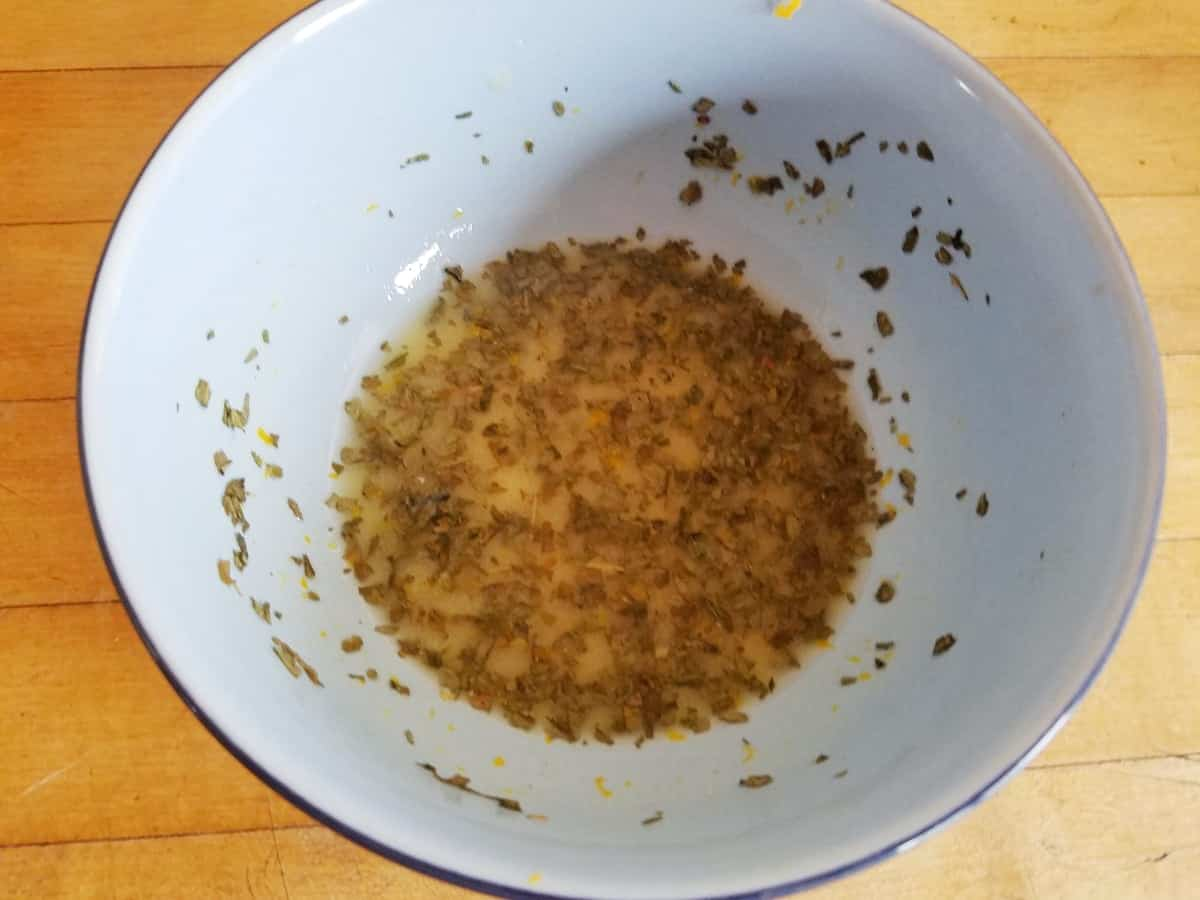 Lemon juice, zest, garlic, vinegar, olive oil and oregano mixture in small white bowl.