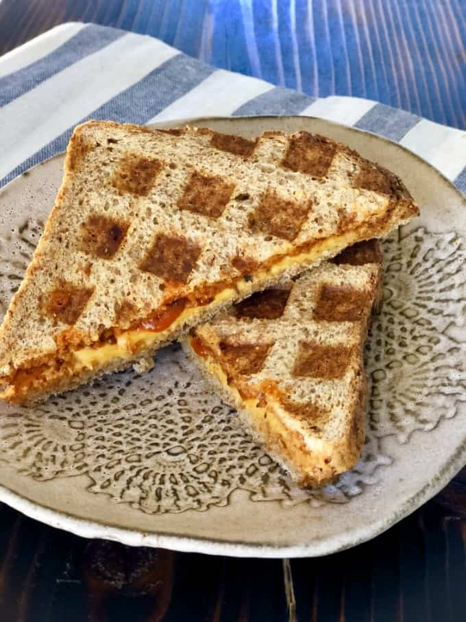 Grilled cheese tomato soup sandwich made in waffle maker on ceramic plate.