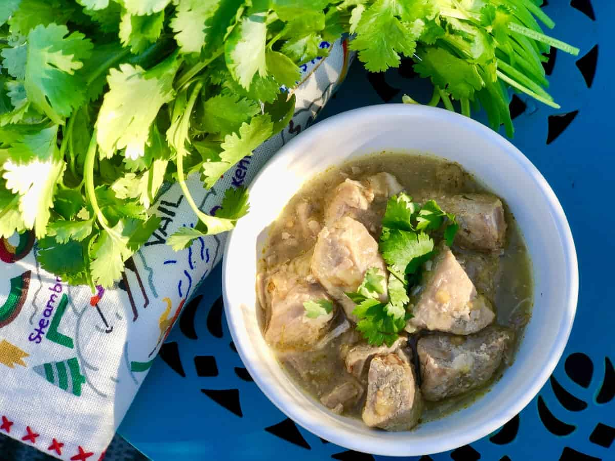 Instantpot green chili pork in white bowl with fresh cilantro
