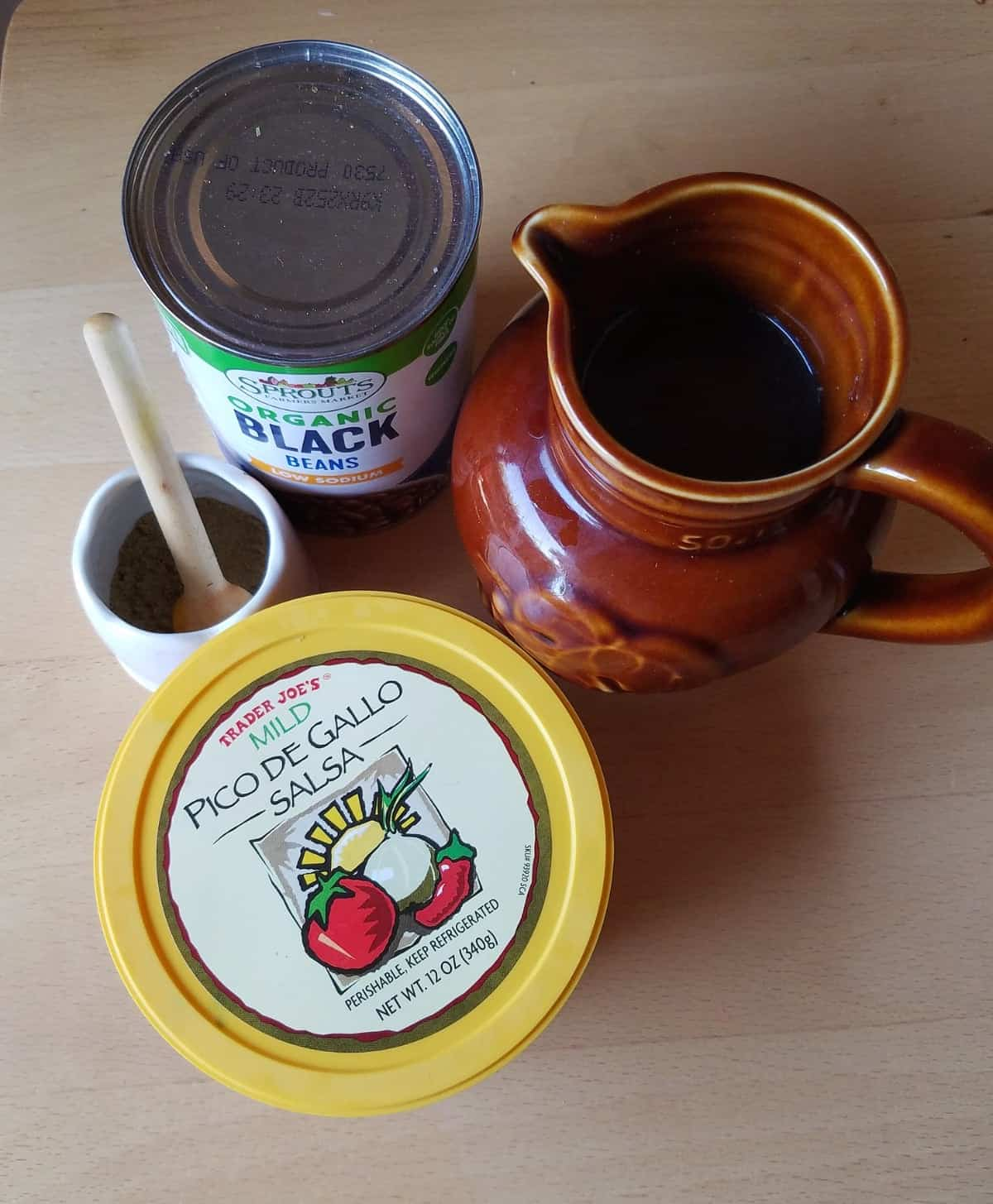 Can of black beans, red wine, pico de gallo and spices for making black bean soup.